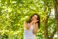 Menopausal woman rests on folded hands. Menopausal woman standing in a park rests on folded hands leaning against her cheeks as if she were sleeping Stock Photography