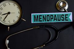 Menopause on the paper with Healthcare Concept Inspiration. alarm clock, Black stethoscope. royalty free stock photo