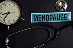 Menopausia en el papel con la inspiración del concepto de la atención sanitaria despertador, estetoscopio negro foto de archivo libre de regalías
