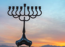 Menorah against background of cloudscape. Silhouette of menorah traditional candelabra for Hebrew Holiday against the colorful background of cloudscape at Stock Image