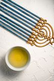 Menorah brass Hanukkah with blue candles and butter in a bowl on a white table. Vertical Royalty Free Stock Image