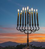 Menorah with burning candles. Is traditional symbol for Hebrew Holidays and celebration of Hanukkah. Background of night or dawn sky, selective focus on menorah royalty free stock image