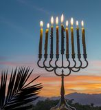 Menorah with burning candles. Is traditional symbol for Hebrew Holidays and celebration of Hanukkah. Background of night or dawn sky, selective focus on menorah stock image