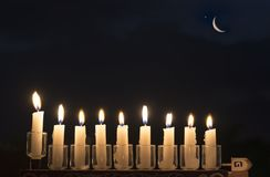 Menorah with burning candles. Is traditional symbol for Hebrew Holidays and celebration of Hanukkah. Background of night sky. English translation for Hebrew stock photos