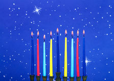 Menorah burning, close up. A nine-branched menorah also called a Chanukiah or Hanukiah burning candles to celebrate Hanukkah against a blue starry background stock photos