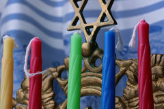 Menorah candles. Colorful menorah candles and a menorah in front of a blue and white tallit Stock Photos