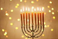 Menorah with candles for Hanukkah. Against defocused lights Royalty Free Stock Photo