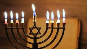 Menorah with candles for Hanukkah against defocused lights,. Close up stock footage