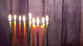 Menorah with candles for Hanukkah against defocused lights Selective soft focus,. Menorah with candles for Hanukkah against defocused lights, close up Selective stock footage