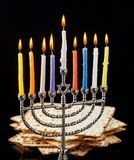 Menorah with candles for Hanukkah on black background. Menorah with lighted candles for Hanukkah on a black background. Matza in the background Royalty Free Stock Photography
