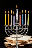 Menorah with candles for Hanukkah on black background. Menorah with lighted candles for Hanukkah on a black background. Matza in the background Stock Images
