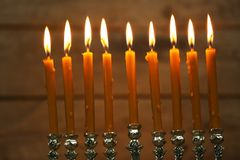 Menorah with candles for Hanukkah. On blurred wooden background, close up Stock Photos
