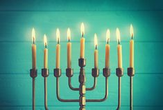 Menorah with candles for Hanukkah. On blurred wooden background, closeup Stock Photo