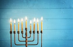 Menorah with candles for Hanukkah. On blurred wooden background Stock Photo
