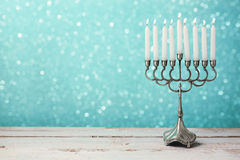 Menorah with candles for Hanukkah celebration over bokeh background Stock Images