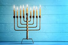 Menorah with candles for Hanukkah. On table against wooden background Royalty Free Stock Image