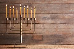 Menorah with candles for Hanukkah on table. Against wooden background royalty free stock photo