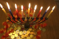 Menorah with candles flowers and chocolate coins Hanukkah and Judaic holiday symbol. Menorah with colored candles flowers and chocolate coins Hanukkah and Judaic Stock Image