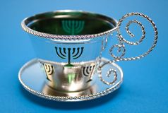 Menorah Cup and Saucer. On the blue background Stock Photo