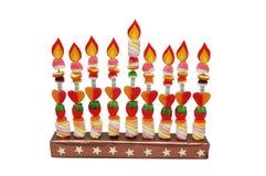 Menorah de Hanukah hecho de los caramelos con la llama de papel imagenes de archivo