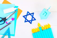 Menorah, dreidel, sevivon, the star of David with their own hands on a white wooden table. DIY for a child. Celebration of Chanuka. H royalty free stock images