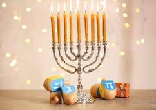 Menorah with dreidels for Hanukkah. On table against defocused lights royalty free stock photos