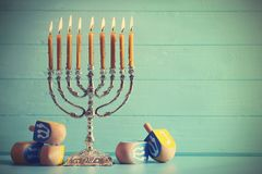 Menorah with dreidels for Hanukkah on table. Against wooden background Royalty Free Stock Photos