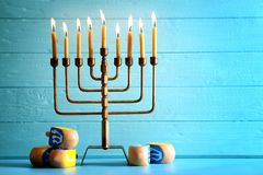 Menorah with dreidels for Hanukkah on table. Against wooden background Stock Photos