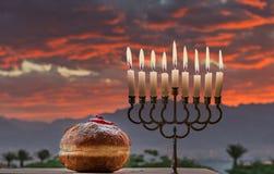 Menorah e os anéis de espuma doces são símbolos judaicos do feriado do Hanukkah foto de stock