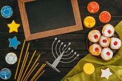 Menorah and frame for hanukkah. Top view of frame, menorah, donuts and cookies with star of david on wooden tabletop, hanukkah celebration Stock Images