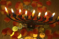 Menorah with lighted candles and chocolate coins Hanukkah and Judaic holiday symbol. The menorah with lighted candles and chocolate coins Hanukkah and Judaic Royalty Free Stock Photography