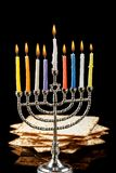 Menorah with candles for Hanukkah on black background. Menorah with lighted candles for Hanukkah on a black background. Matza in the background Stock Photos
