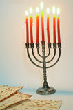 Menorah with lit candles. Menorah with red candles and pieces of Matzo royalty free stock photos