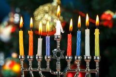 Menorah met kaarsen voor Chanoeka op de achtergrond van de Nieuwjaarboom Stock Afbeelding