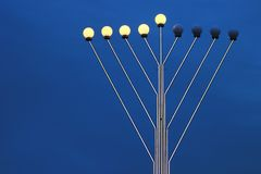 Menorah street lamp at Hanukkah time against evening sky. Background Stock Photos