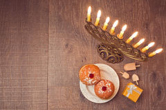 Menorah and sufganiyot on wooden table for Hanukkah celebration. View from above. Menorah and sufganiyot on wooden table for Hanukkah celebration