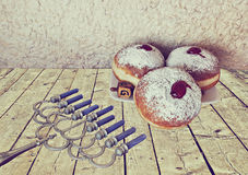 Menorah and sweet donuts are Hanukkah Jewish holiday symbols Stock Photos
