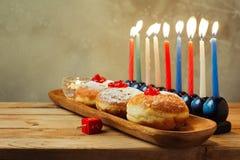 Menorah y buñuelos para el día de fiesta judío Jánuca en la tabla de madera imagen de archivo