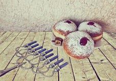 Menorah y los anillos de espuma dulces son símbolos judíos del día de fiesta de Jánuca fotos de archivo