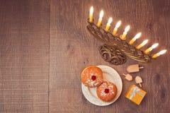 Menorah和sufganiyot在木桌上光明节庆祝的 在视图之上 图库摄影