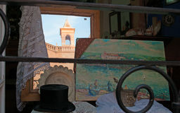 Menorca, Balearic Islands, Spain. The bell tower of El Roser Church seen through the window of an antique shop in Ciutadella on July 7, 2013. El Roser Church was Royalty Free Stock Image