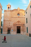 Menorca, Balearic Islands, Spain. A child on a tricycle in front of El Roser Church in Ciutadella on July 7, 2013. El Roser Church was built in 1705 Stock Images