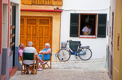 Menorca, Balearic Islands, Spain. Local people seated and talking in the streets of Ciutadella on July 7, 2013. Ciutadella is the former capital city of Menorca Royalty Free Stock Photo