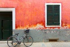 Menorca Ciutadella red grunge facade texture. Menorca Ciutadella red grunge facade wit bicycle at Balearic islands royalty free stock images