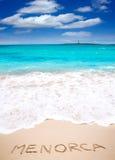 Menorca ord som är skriftligt på sand av den medelhavs- stranden Royaltyfri Fotografi