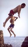Menorca, Spain - September 8: Man and kid jumping from cliff into the sea, in September 8, 2014 in Menorca, Spain Stock Photo