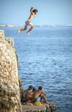 Menorca, Spain - September 8: Young man jumping from cliff into the sea, in September 8, 2014 in Menorca, Spain Royalty Free Stock Photo