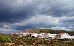 Menorca Urbanization. Classic Small Menorca Urbanization between Hills under Cloudy Skies Outdoors. Balearic Islands Stock Photography