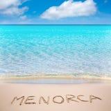 Menorca-Wort geschrieben auf Sand des Mittelmeerstrandes Stockfotos