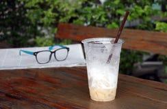 Menos café do cappuccino no copo plástico e focaliza para fora o spectacl imagem de stock royalty free